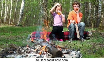 Boy and little girl sit, they drink juice and watch at bonfire