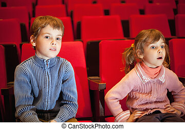 boy and little girl sitting on armchairs at cinema, girl has...
