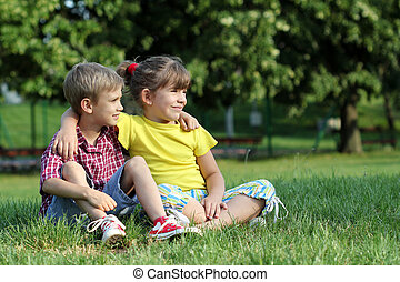 boy and little girl sitting on grass in park