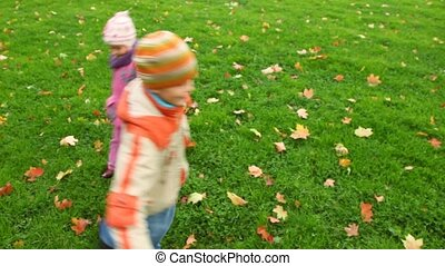 boy and little girl spinning in autumn park, join hands