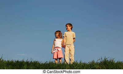 Boy and little girl stand on grass, comes their mother, click clapperboard