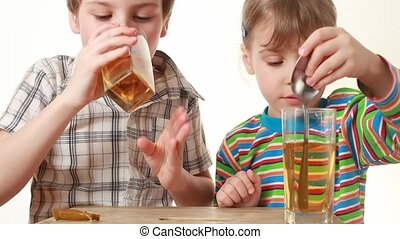 boy and little girl stiring and drink juice