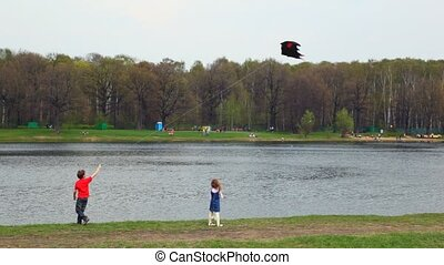 boy and little girl with kite in bat form on bank of river
