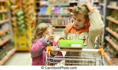 boy and little girl with shopping trolley looks at goods box in supermarket