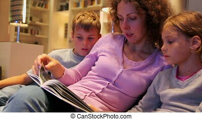 Boy and little girl with their mother sit on sofa and read book
