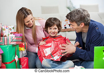 Boy And Parents Opening Christmas Present
