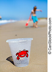 Boy and plastic bucket on beach