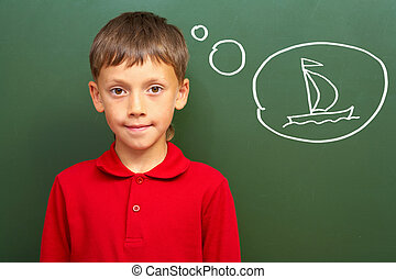 Portrait of smart lad by the blackboard thinking of sail and looking at camera