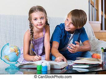 boy and sister studying with books - Teenage boy and younger...