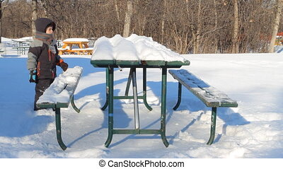 Boy and snow - Boy removes snow from a table in the park in...