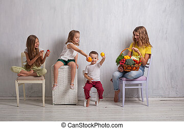 boy and three girls with a basket of vegetables and fruits