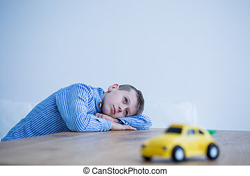 Boy and toy car on a table