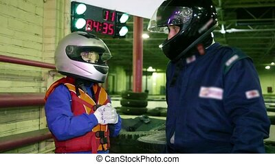 Boy and trainer in racing helmets hit his fists into hand