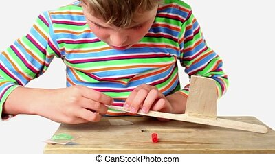 Boy apply adhesive and attach tail to wooden aircraft, he...