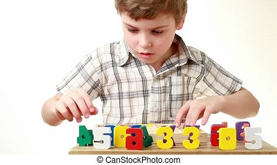 boy arranges wooden multicolor figures numbers on table