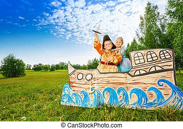 Boy as pirate and princess girl stand on ship