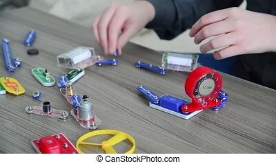 Boy assembles the electrical circuit from constructor - Teen...