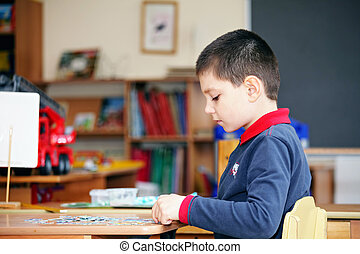 Boy assembling puzzles sideview