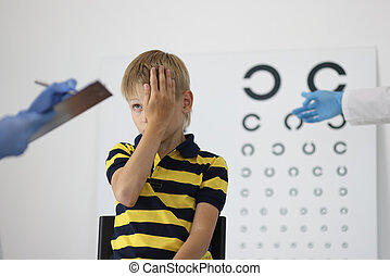 Boy at an ophthalmologist's appointment closes one eye and ...
