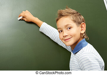 Boy at blackboard - Portrait of smart schoolchild by the...