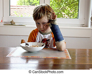 boy at breakfast with cast on his broken arm
