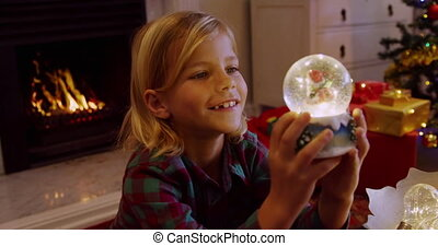 Side view close of a smiling young Caucasian boy holding a snow globe in the sitting room at Christmas time and looking at it, a decorated Christmas tree and open fire in the background