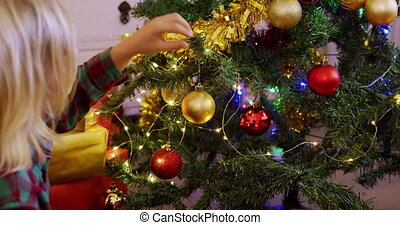 Side view close up of a young Caucasian boy decorating the Christmas tree in his sitting room with baubles and fairy lights at Christmas time