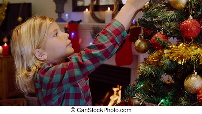 Side view of a young Caucasian boy decorating the Christmas tree in his sitting room with baubles at Christmas time
