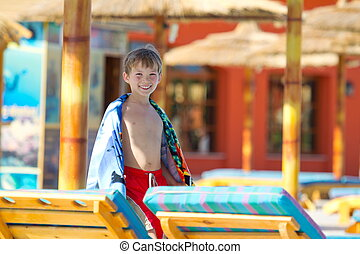 Boy walking on patio at a resort.