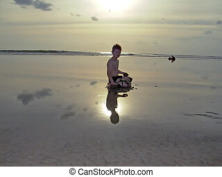 boy at the beach with Sunset and reflections