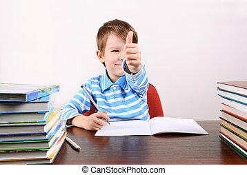boy at the desk shows a hand with a thumb up
