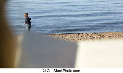 Boy at the water playing with wooden stick, mother reading