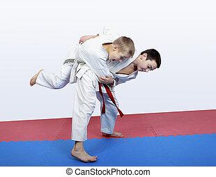 Boy athlete sash makes hip throw - Boy athlete with a red...