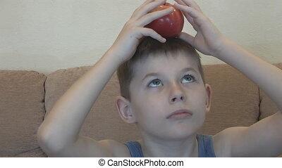 Boy balancing an apple on his head