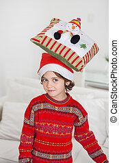 Boy Balancing Cushion On Head During Christmas