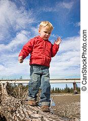 Boy balancing on log