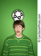 Boy balancing soccer ball.