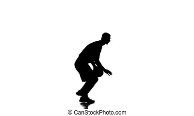 Boy basketball player makes a feint with the ball. Silhouette