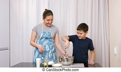 boy beats eggs with a whisk under the supervision of a woman in the kitchen.