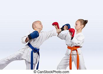 Boy beats punch girl standing in the rack karate