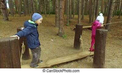Boy blond and girl child child with glasses having fun on the playground in the park. Little children have fun weekend together. Autumn day in the park