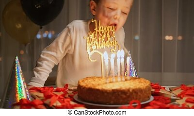 Boy blow out candles on birthday cake