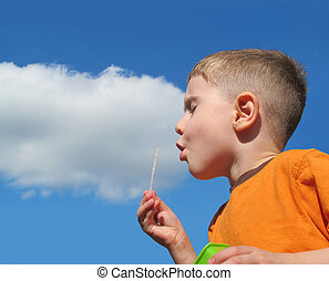 Boy Blowing Bubbles in Sky with Cloud