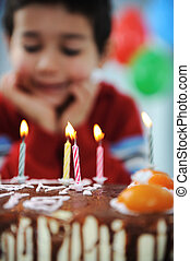 Boy blowing candles on cake, happy birthday party