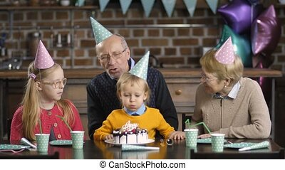 Boy blowing candles on cake with his grandparents