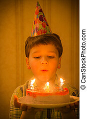 Boy blowing to burning candles at birthday cake
