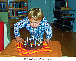 boy blows out his birthday candles at his birtday
