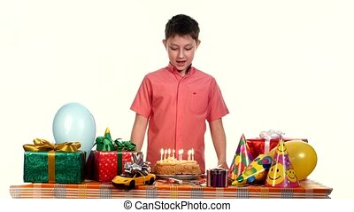 Boy blows out the candles on  cake. Table strewn with gifts and balloons. white background