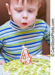 boy blows out the candles