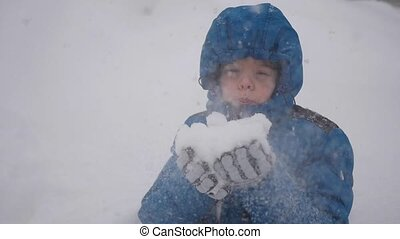boy blows snow with hands closeup in slowmo. Snow storm